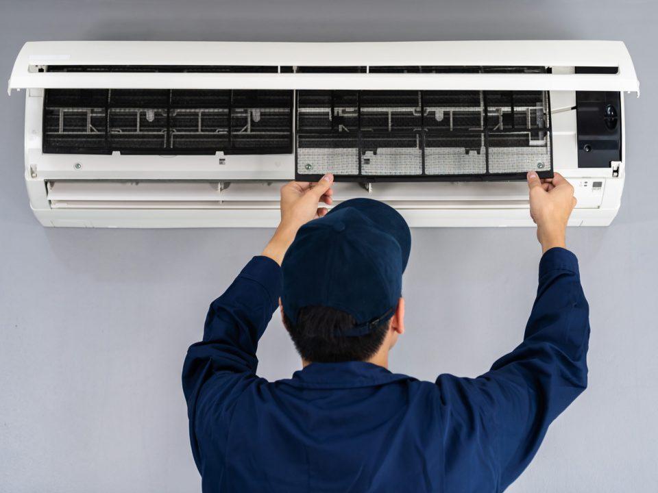 técnico manipulando un aparato de aire acondicionado